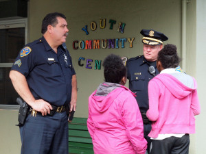 Officers Kaprosch and Redmond chat with children in front of the Garfield Park clubhouse, where the book corner is located.