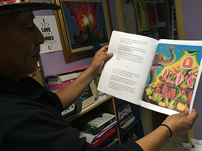 Argueta holding a book from the upcoming story of Manyula. Photo by Lydia Chávez