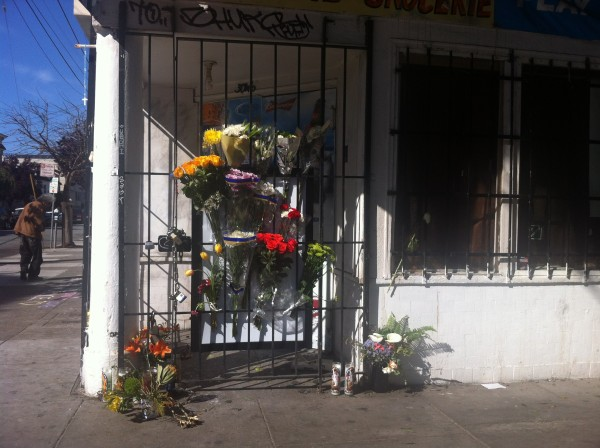 Neighbors have been stopping by to leave flowers on the gate of the store below the apartment that caught in flames two weeks ago. Photo by Andrea Valencia.