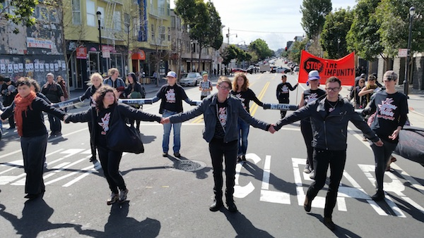 A human chain, that blocked entrance to Mission Police Station, moves down Valencia Street. Photo by Daniel Hirsch.