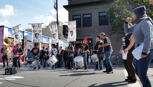Loco Bloco drummers hold banners with four officers involved in police shooting of Alex Nieto. Photo by Daniel Hirsch.
