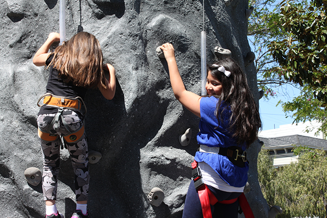 Sisters Araceli, 5, and Ariela, 9, tackle the climbing wall together. Photo by Laura Wenus