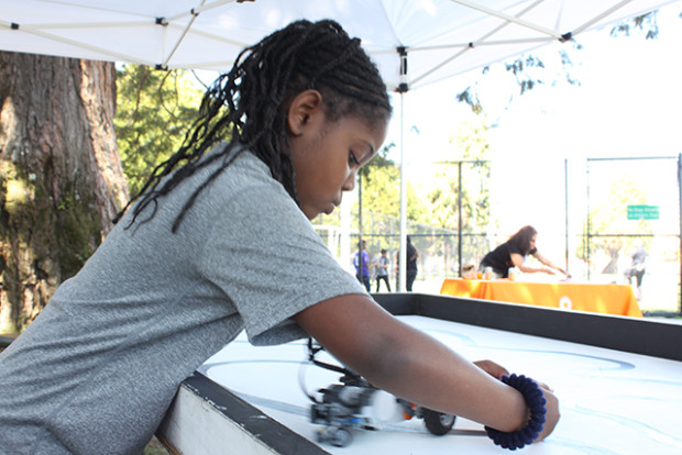 Ariel, 7, tests the obstacle-detecting abilities of a robot built by Garfield Square's robotics students. Photo by Laura Wenus
