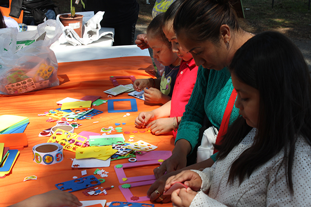 Kids (and one parent) decorate photo frames at the Mission Neighborhood Centers' table. Photo by Laura Wenus