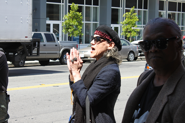 A bystander on Valencia street claps to the rhythm of the protesters' chants. Photo by Laura Wenus