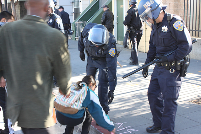 Police move a chalk-writing protester off the sidewalk. Photo by Laura Wenus