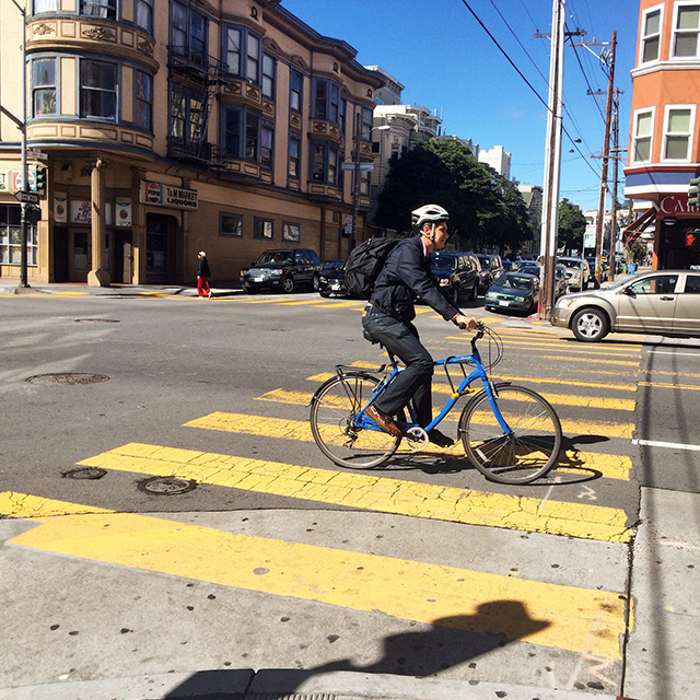 Cyclist on blue bike. Photo by Elise Marie Collins