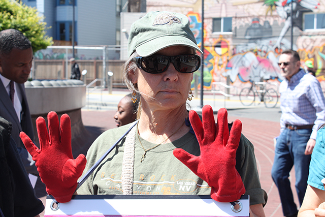 Martha Hubert, holds up red-gloved hands to symbolize the blood that officers who shoot civilians or stand by without intervention have on their hands. Photo by Laura Wenus