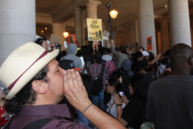 A protester adds his shout to the din inside City Hall. Photo by Laura Wenus