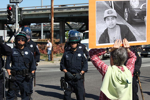 A protester holds a sign with a photo of  police shooting victim Amilcar Perez Lopez as police keep the march from advancing down 5th street. Photo by Laura Wenus