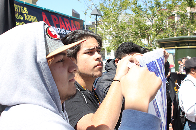 Jose Medina, left, and Jamal Jaser, hold a poster at 24th and Mission. Photo by Laura Wenus