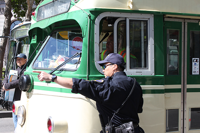 An officer directs public transit along Market street, most of which is blocked by protesters. Photo by Laura Wenus