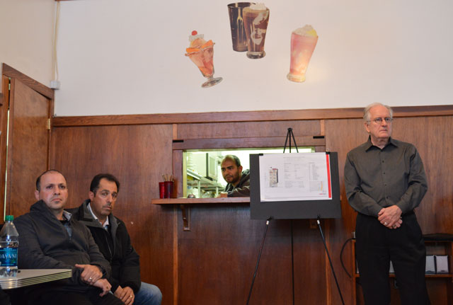 Architect Warner Schmalz, right, and laundromat owner Johnny Muhawieh, second from right, listen to audience members speaking out against their proposed development.
