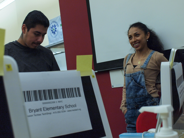 Ramiro Quezada and Mercy Mena checking in computers from Bryant Elementary School.