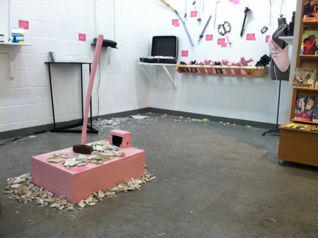 Pieces of the smashed-up urinal still decorate the gallery space, and an arsenal of pink tampon-shooting Nerf guns (along with other assorted weaponry) decorates a side wall. Photo by Joe Rivano Barros.