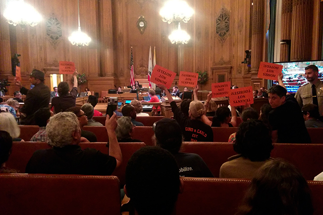 Members of the public hold signs Inside the board of Supervisors at a discussion of short term rentals in 2015.