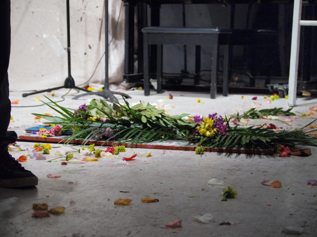 The hole in the art house floor, covered by a plank and flowers at the end of the event. One guest did accidentally fall in the hole during the event, just after 7 p.m., bumping her knee. She had been headed to the piano with sheet music.
