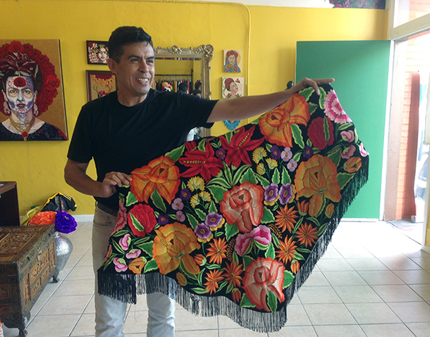 Marcos Salazar with a hand-embroidered shawl at Frida's Closet.