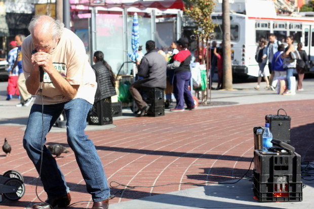 Gary McElroy plays harmonica outside the 24th Street BART Station.