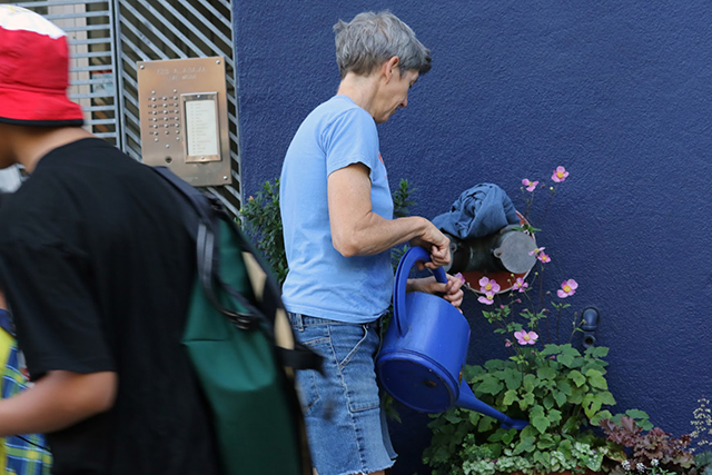 Eileen Seymour starts her day on this unseasonbly hot fall day to water the garden in front of her building on Alabama street.