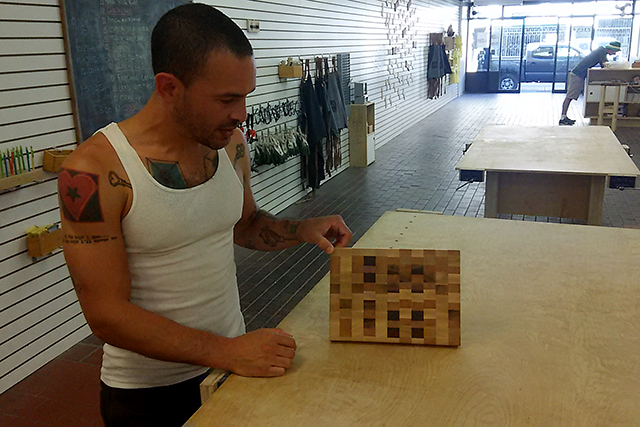 Montoya shows off a cutting board made in one of his classes. Photo by Laura Wenus
