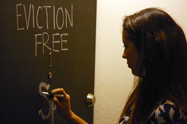 La inquilina Bailey Nakano retoca un llamado, en gis, en la puerta de su departamento.