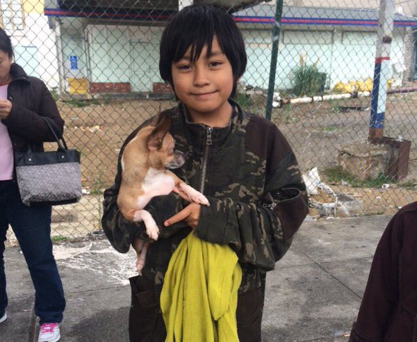 "10-year-old Giovanni with the dog that barked when the fire started. ""My dog saved us."" Photo: Laura Waxmann."
