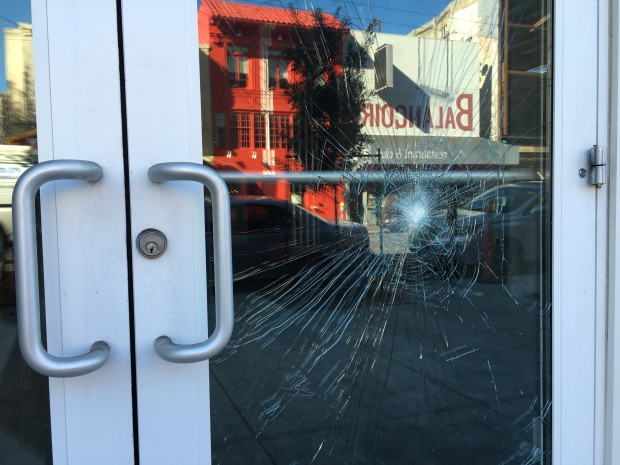 The Mission Street entrance door of Vida Apartments smashed by an unknown suspect last week. Photo by Joe Rivano Barros.