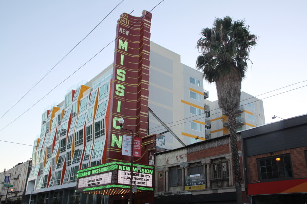 The refurbished New Mission sign, with the Vida Apartments in the background. Photo: Laura Waxmann / Mission Local.