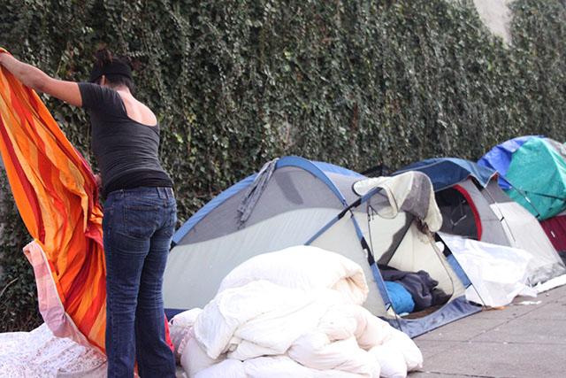 A woman named Trina tidies her spot at the homeless encampment where she lives. Photo by Laura Waxmann