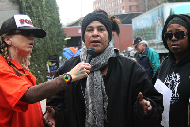 Trina, a resident of the homeless encampment on Trainor Street between 14th and Division, stands next to Lisa Gray-Garcia (left) and homeless rights advocate Queen Nandi (right) while speaking at a press conference on homelessness organized by Poor Magazine. Photo by Laura Waxmann