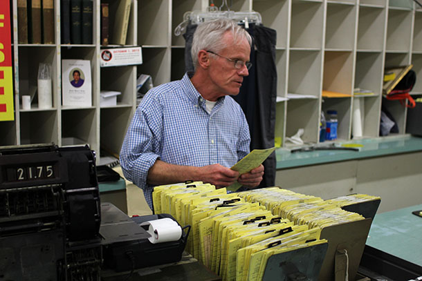 John Thompson selects a customer's card out of a thick roster. Photo by Laura Wenus