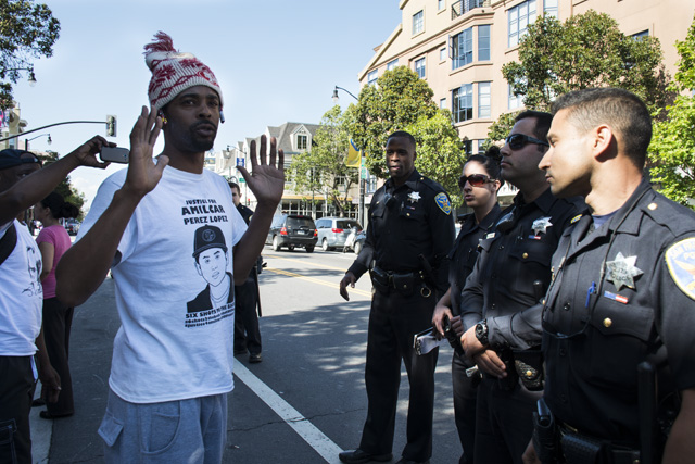 Sellassie Blackwell, one of the hunger strikers, confronting officers on Sunday. Photo by Lola M. Chavez