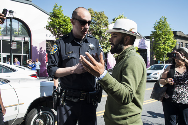 Edwin Lindo (right) speaking with a police officer on Sunday. Photo by Lola M. Chavez