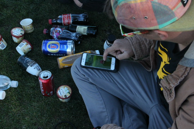 Players sitting on the grass and drinking at Dolores Park for the July 20, 2016, Pokemon Go crawl. Photo by Joe Rivano Barros.