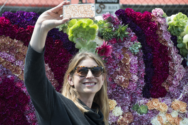 A woman takes a selfie in front of Mission de Flores's wall of flowers display. Photo by Lola M. Chavez
