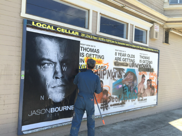 A worker plastering over the graffitied Viceland ads. Photo by Cynthia Lasden.