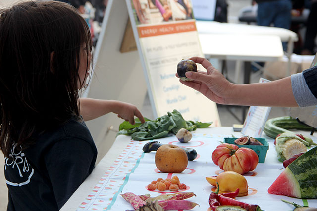 Kids learning about produce at the BiRite stand, starring one beautifully multifaceted tomato front and center