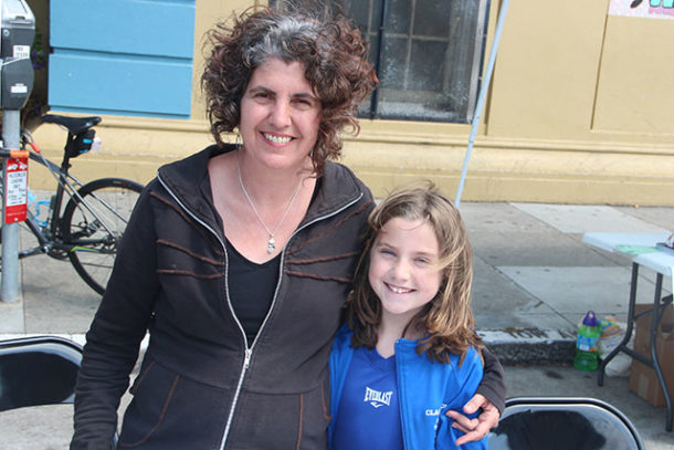 """Former CCSF instructor Victoria Mara Heilweil and her daughter at Heilweil's table, where people can write postcards to local representatives to try to improve the lot of teachers. Says Heilweil: """"San Francisco Really is at the crossroads of this crisis."""""""