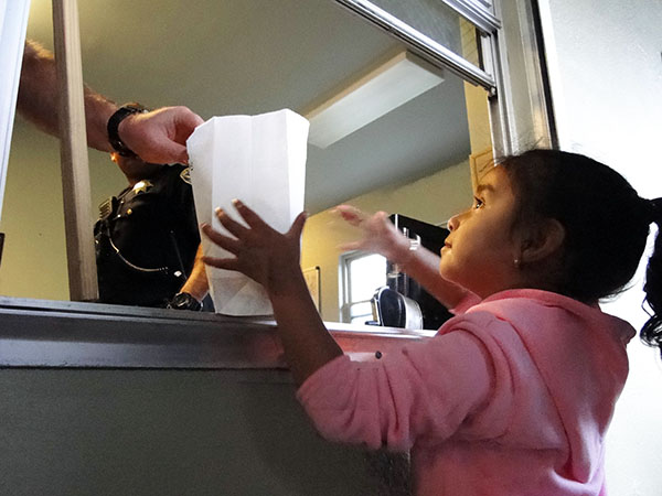 Ingrid Kauil, 5, receives her popcorn from Mission Station officers. Photo by Sonner Kehrt