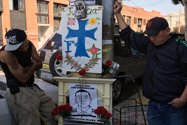 John Visor (left) and Jose Gongora Pat, the younger brother of Luis Gongora Pat,    stand in front of a memorial honoring the slain man on September 7. Photo by Laura Waxmann