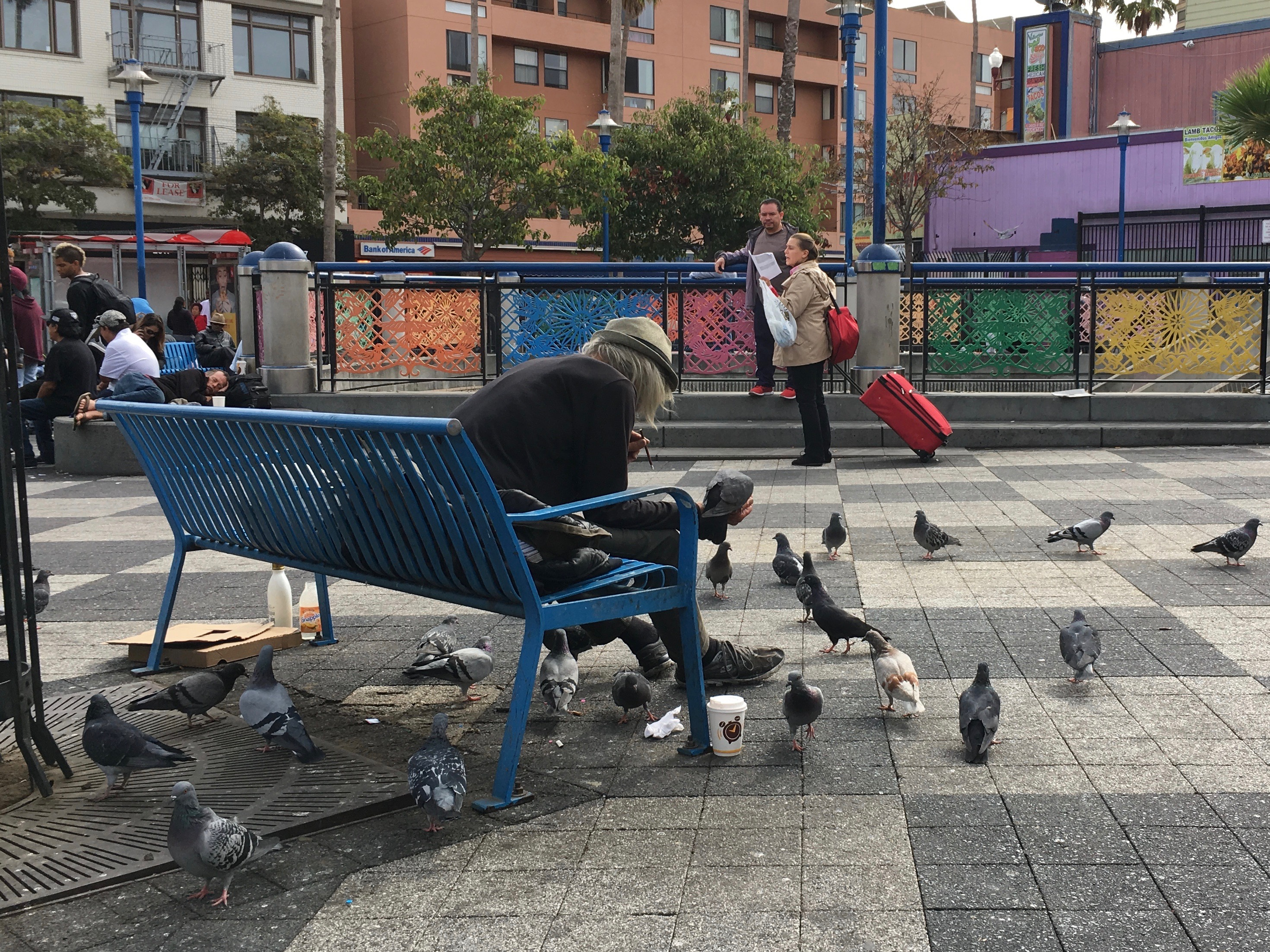 A regular at the 16th Street Bart Plaza feeding pigeons with rice. Photo by Joe Rivano Barros.