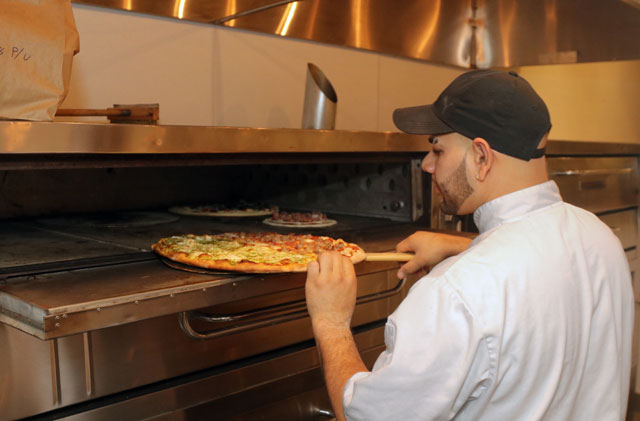 Jose Mendoza removes a freshly cooked pizza from the brick oven and assures perfect cooked texture.