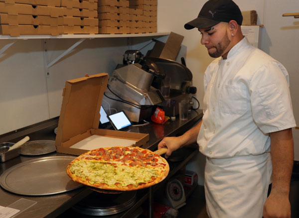 Jose Mendoza assures the two part pizza is perfect before delivery to the delight of waiting diners.