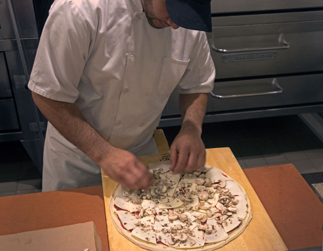 Jose Mendoza carefully places the toppings to create a delight for the eye and palate.
