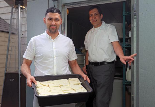 Gustavo and Esteban Lopez retrieve freshly sliced Mozzarella.