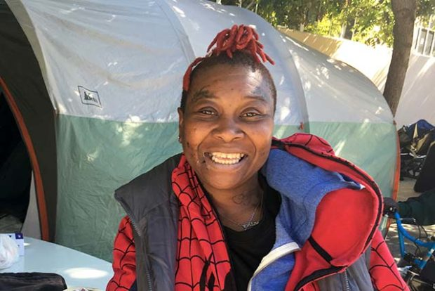Kimberley Walley, displaced from the Graywood hotel at 3308 Mission St. by a five-alarm fire, stands in front of the 16th and Shotwell street tent encampment where she most recently lived. Photo by Laura Waxmann