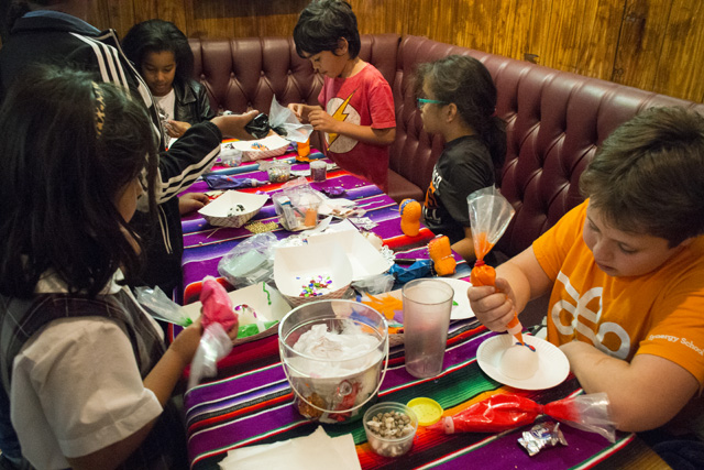 Children decorating sugar skulls. Photo by Lola M. Chavez
