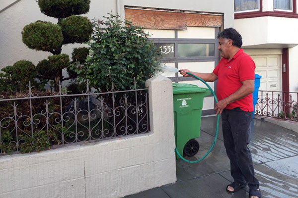 Bert Pelaez watering his front yard on Alabama Street. Photo by Lydia Chávez