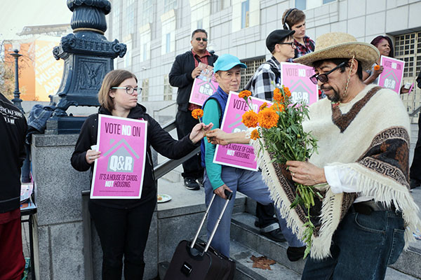 Miguel Carrera of the Coalition on Homelessness, passes out marigolds. Photo by Serginho Roosblad